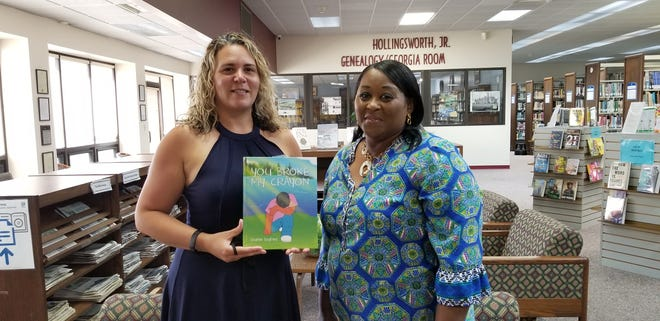 """The Screven County Library receives a donation from a local author named Sharon Bedford who wrote a children's book titled """"You Broke My Crayon"""" about bullying. The donation was made on July 29 as Bedford (right) is pictured with Branch Manager Amber Ball."""