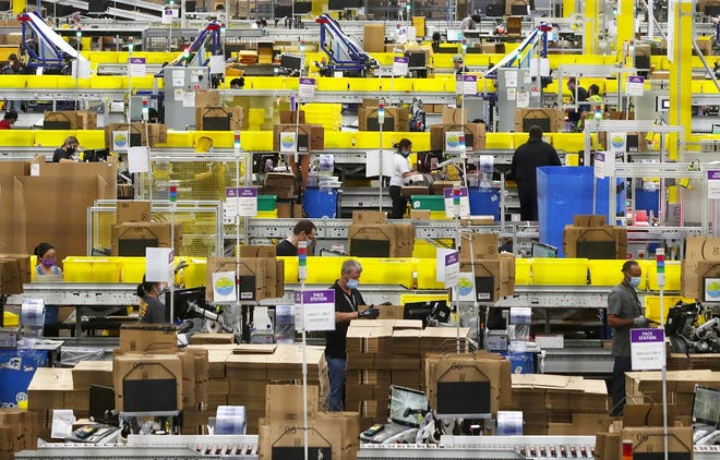 Employees at packing stations are seen at Amazon's Kent, Washington, fulfillment center. The retail giant charted its third consecutive quarter of $100-billion-plus sales.