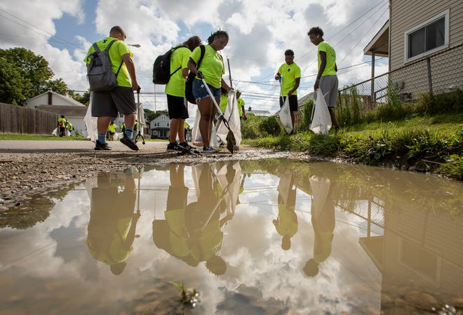 Nicole Hunt, 16, center, plucks garbage from a mud puddle in the Hilltop neighborhood as she works alongside other teens and young adults from YMCA of Central Ohio's Earth Service Corps. The program is part of the mayor's summer initiative to give young people jobs and to cut back on violence.