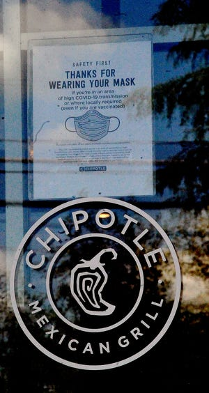 A sign on the door of Chipotle in Wooster encourages patrons to mask up.