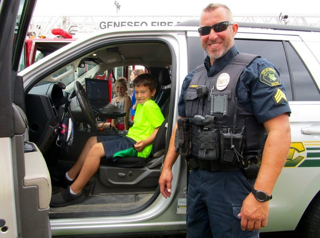 Geneseo Police Sgt. Jamison Weisser was at the Geneseo Athletic Field with his squad car and allowed the kids to sit in the front seat of the vehicle. Taking their turn are Lillian Rowold, passenger, and Jensen Peacock, in the driver's seat.