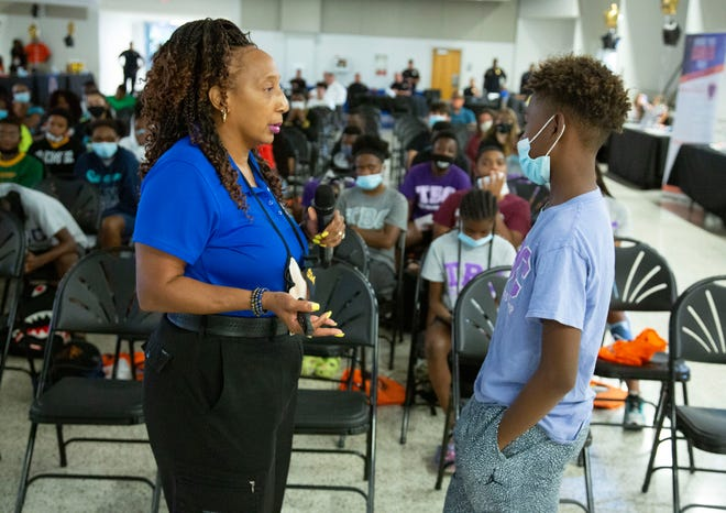 Tallahassee Deputy Chief Tonja Bryant-Smith, president of NOBLE North Florida Chapter, is assisted by Messiah Bolders, 12, with a demonstration on things that affect encounters with law enforcement at Lakeland Police Department's Teen Summit at the Lake Mirror Center in Lakeland on Friday .
