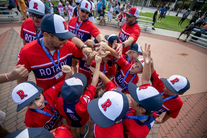 Ocala's Rotary Reds give a cheer after parading around Ocala's Downtown Square for the opening ceremonies of the 2021 Cal Ripken 8U Machine Pitch World Series.