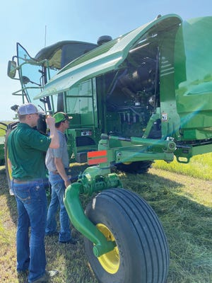 Zach Wilson (BTI) visits with Derek Waters (St. John) as they look over the John Deere W235 windrower prior to demoing it during BTI's Hay Day event on July 28 just north of St. John along U.S. Highway 281.