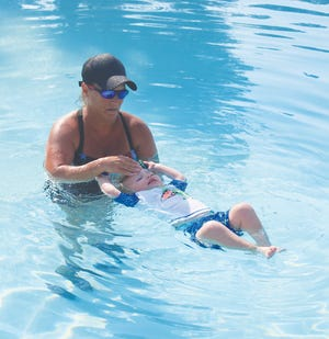 Pratt Swim Team coach and private lesson instructor Tonja Harrison helps Sage Eddy, 20 months, flip to his back and float during survival skills lessons Friday at Park Hills Country Club pool.