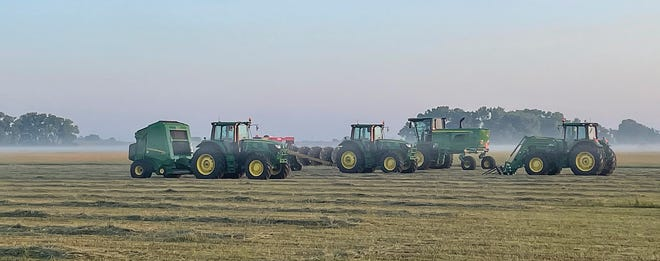 An early-morning, summer fog lifts slowly over a hay field north of St. John on Wednesday where BTI equipment stands ready for special Hay Day exhibition.