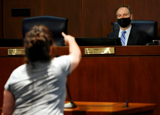 St. Louis County Executive Sam Page listens to Angelina Isaac criticize the mask mandate during public comments during a St. Louis County Council meeting on Tuesday, July 27, 2021, in Clayton, Mo. Laurie Skrivan/St. Louis Post-Dispatch via AP