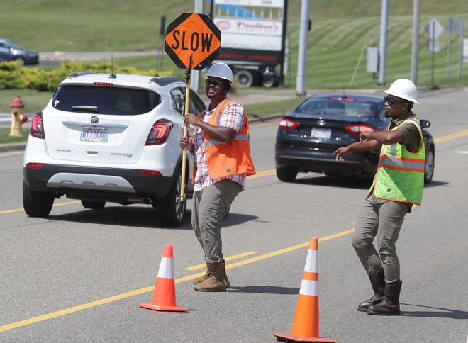 Rashaad McWilliams, left, and Kiante Williams, have been entertaining motorists with their dance moves while providing traffic control for fiber optic cable installation. The pair work for Emergent Technologies, a subcontractor for AT&T.