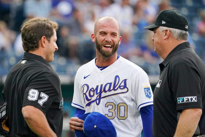 Former Kansas City Royals pitcher Danny Duffy (30), who was traded to the Los Angeles Dodgers last week, laughs with umpires Ben May (97) and Bill Welke (3) after they inspected his hat and glove between innings of a July 16 game.