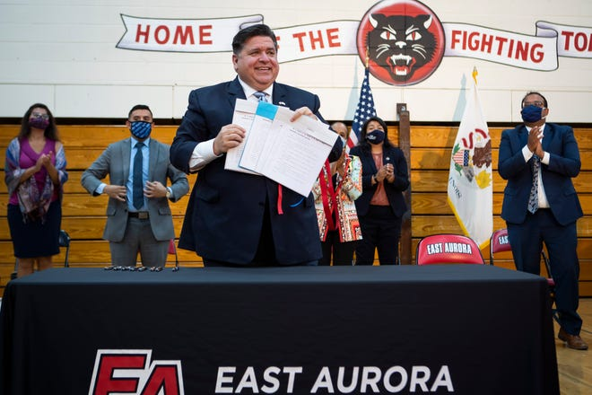 Gov. JB Pritzker smiles after signing legislation Monday that expands protections for immigrant and refugee communities. Pritzker signed the bill at East Aurora High School in Aurora.