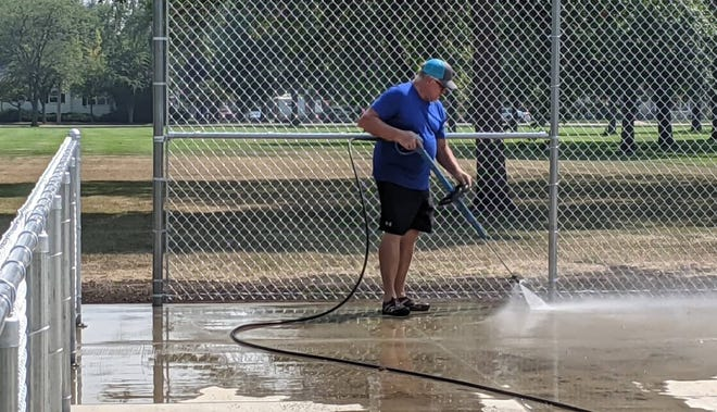 Scott Leitheiser uses a power washer Monday afternoon to get the new pickleball courts at Manor Park ready to be painted. The courts should be ready for use by the middle of the month.