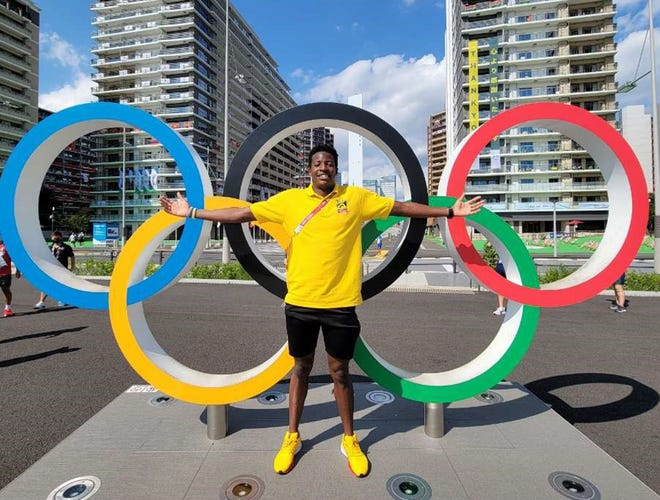 """Atuhaire """"Atu"""" Ambala of Uganda, a Clark University freshman, stands in front of the Olympic rings in Tokyo. Ambala is represented his county in the Olympics, competing in the men's 100-meter freestyle."""
