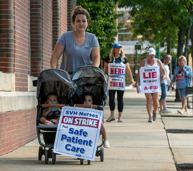 Striking St. Vincent Hospital nurse Katelyn Santillan walks the picket line with her two children Monday, Aug. 2, 2021.