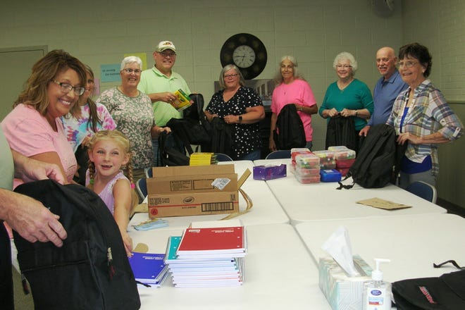 Members of the Broadway United Methodist Church packs book bags to be given from 10 a.m.-2 p.m. Saturday, Aug. 21.