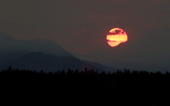 Smoke obscures the sun as it sets behind the Olympic Mountains as seen from Tracyton on Sunday, August 1, 2021.