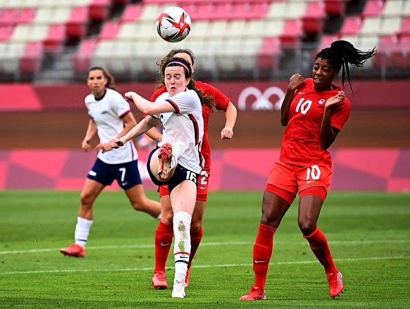 USA's midfielder Rose Lavelle clears the ball ahead of Canada's defender Ashley Lawrence (right) during the Tokyo 2020 Olympic Games women's semi-final football match between the United States and Canada at Ibaraki Kashima Stadium in Kashima on August 2, 2021.
