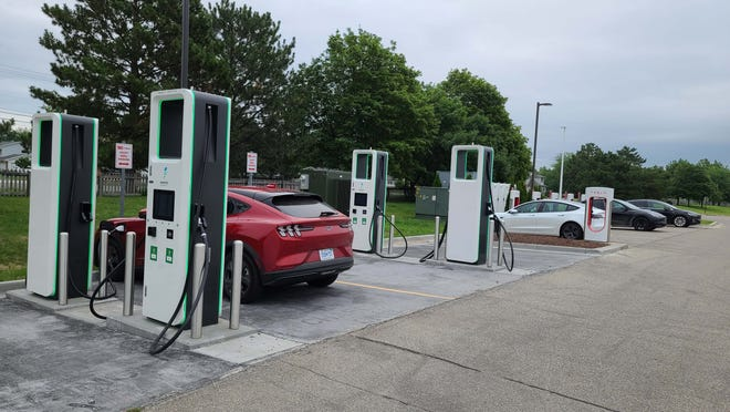 Ford v. Tesla. The 2021 Ford Mustang Mach-E charges at Electrify America station in Bay City next to Tesla chargers in a Meijer parking lot.