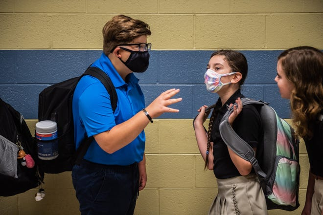 6th graders, Dalton Nixon, 12, left, and Rebekah Walters, 11, wait in line to be directed to their homeroom on the first day of classes at West Bemis Middle school on Monday, Aug 2, 2021 in Jackson, Tenn.