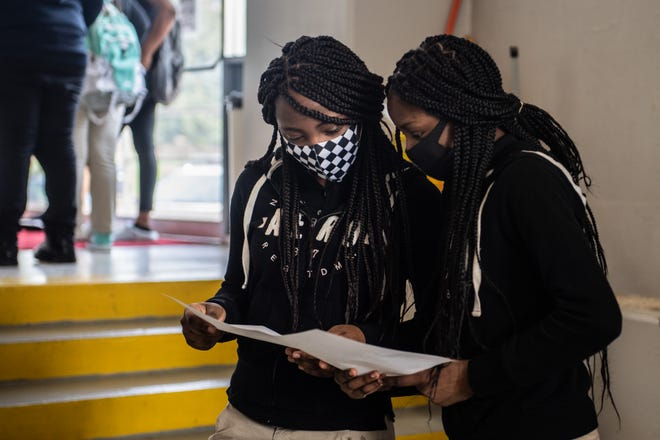 10th grader sisters, Dayona Carpenter-Jones, 15, left, and Da'Siyah Carpenter, 14, look at their class schedules to see how many classes they have together on the first day of classes for Jackson Central-Merry Early College High at Oman Arena on Monday, Aug 2, 2021.