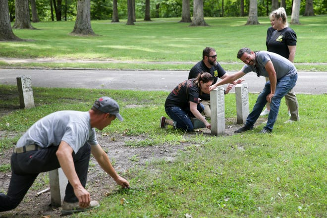 Members of U.S. Army 384th Military Police battalion Headquarters and Headquarters Company work to straighten gravestones at the Indiana Veteran's Home cemetery, Saturday, July 31, 2021 in West Lafayette. The company deployed to Afghanistan from October 2012 to June 2013. The Warrior Reunion Foundation facilitated a reunion for several members of the unit in West Lafayette over the weekend.