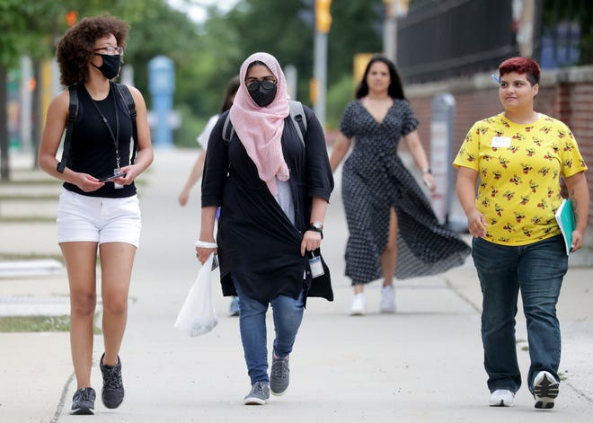 University of Wisconsin-Milwaukee students walk through the campus on Monday. Colleges across the state are working to reevaluate on-campus masking policies in the weeks leading up to the start of the fall semester.