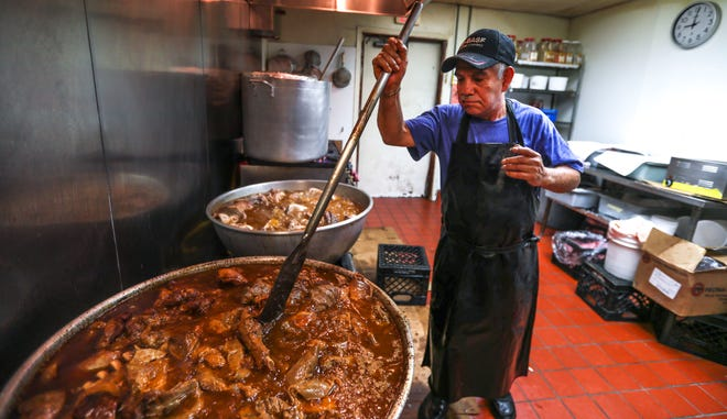 Jose Luis Mejia stirs carnitas as they marinate in July at Carnitas Don Lucho in Milwaukee. About 1,500 pounds of carnitas are served over a three-day period. The 70-year-old Mejia is the restaurant's namesake; his nickname is Don Lucho.