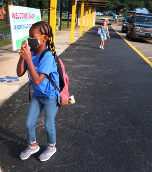 First grader Michelle Humphrey adjusts her mask as she gets ready to enter JR Baker Elementary on her first day of school, on Monday, Aug. 2, 2021.