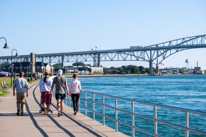 A group of people walk along the boardwalk near the Blue Water Bridge, where the St. Clair River meets Lake Huron, on Aug. 2, 2021, in Port Huron.