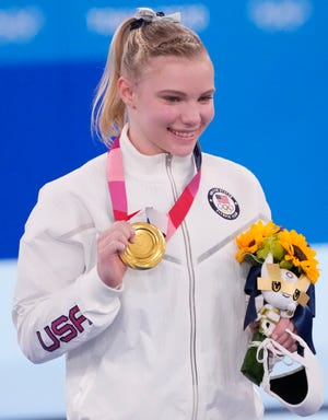 Aug. 2: Jade Carey holds up her gold medal during the ceremony for the women's floor exercise.