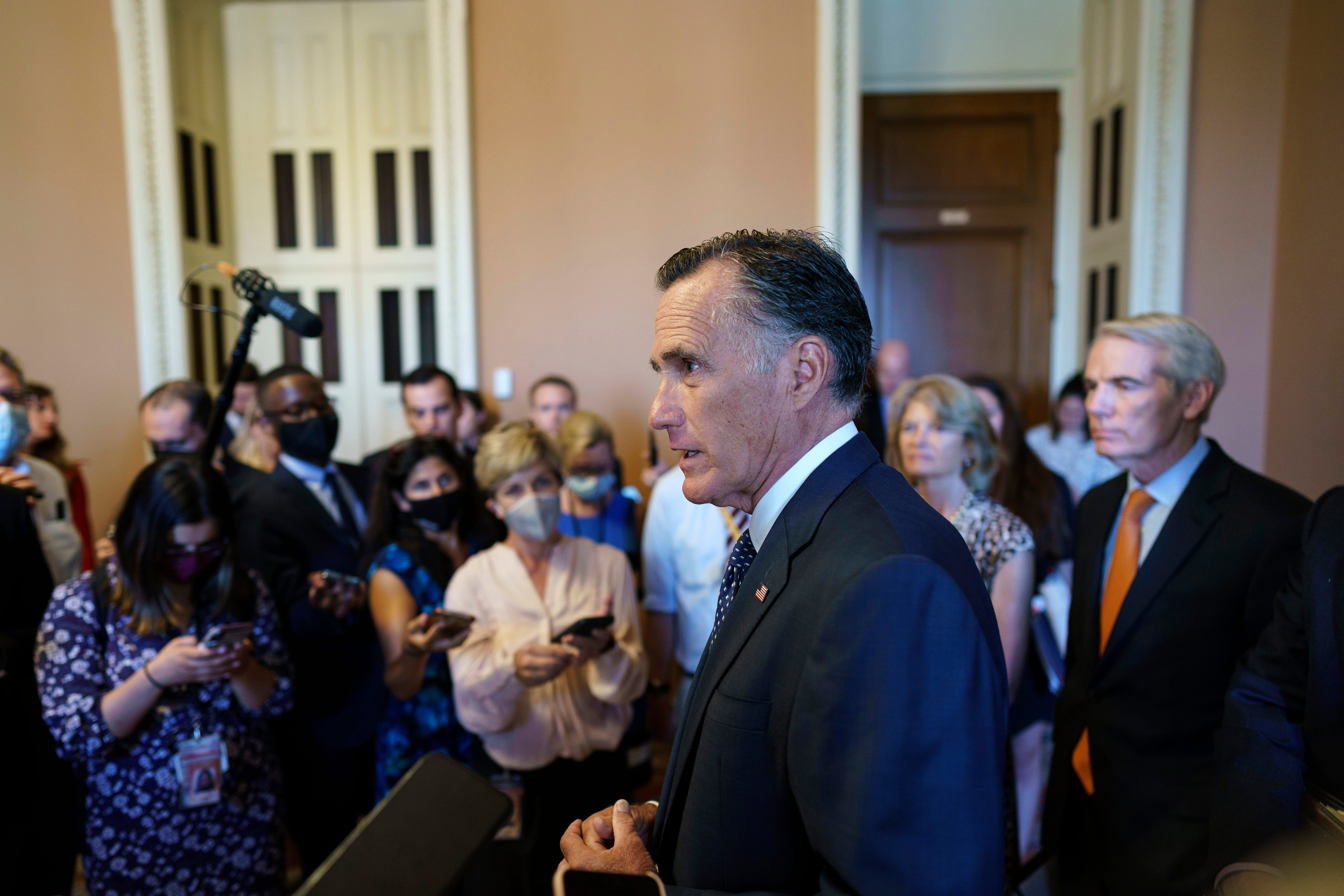 Sen. Mitt Romney, R-Utah, center, and other Senate Republicans negotiating a $1 trillion infrastructure bill with Democrats, announce they have reached agreement on the major outstanding issues and are ready to vote to take up the bill, at the Capitol in Washington on July 28, 2021.