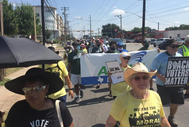 Karen Sterling (front left) and Joni Ashbrook (front right) walk along Lamar Boulevard as part of the Moral March for Democracy from Georgetown to Austin.