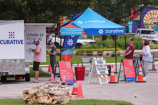 People wait in line for a free COVID-19 test in the parking lot of the Georgetown library on Tuesday. The pop-up has been testing in that location for over a year.