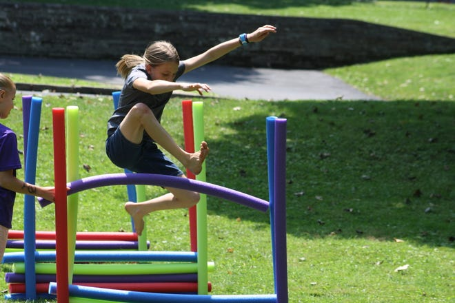 A Olympic-type obstacle course was in place to challenge Alliance-area children on Saturday, July 31, 2021, at Rodman Public Library. Here, a young girl attempts to hurdle over pool noodles set up on one section of the course.