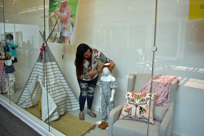 Sydney Petersen, owner of Bizzy's Boutique, adjusts the headband on a mannequin in the front window of her new store at the North Grand Mall, which will open in September.