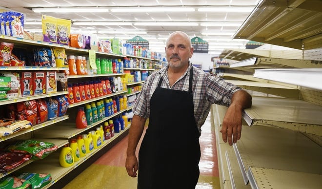Owner of Story City Market David Wooldridge poses in front of empty shelves at the store that is going out of business Thursday, July 22, 2021, in Story City, Iowa.