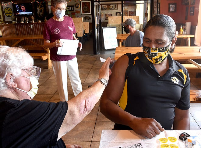 Sandy Thomas, a registered nurse for Columbia/Boone County Public Health and Human Services, places a Band-Aid on the arm of Isaac Prince of Columbia after giving him a COVID-19 vaccination Aug. 3 at Como Smoke & Fire.