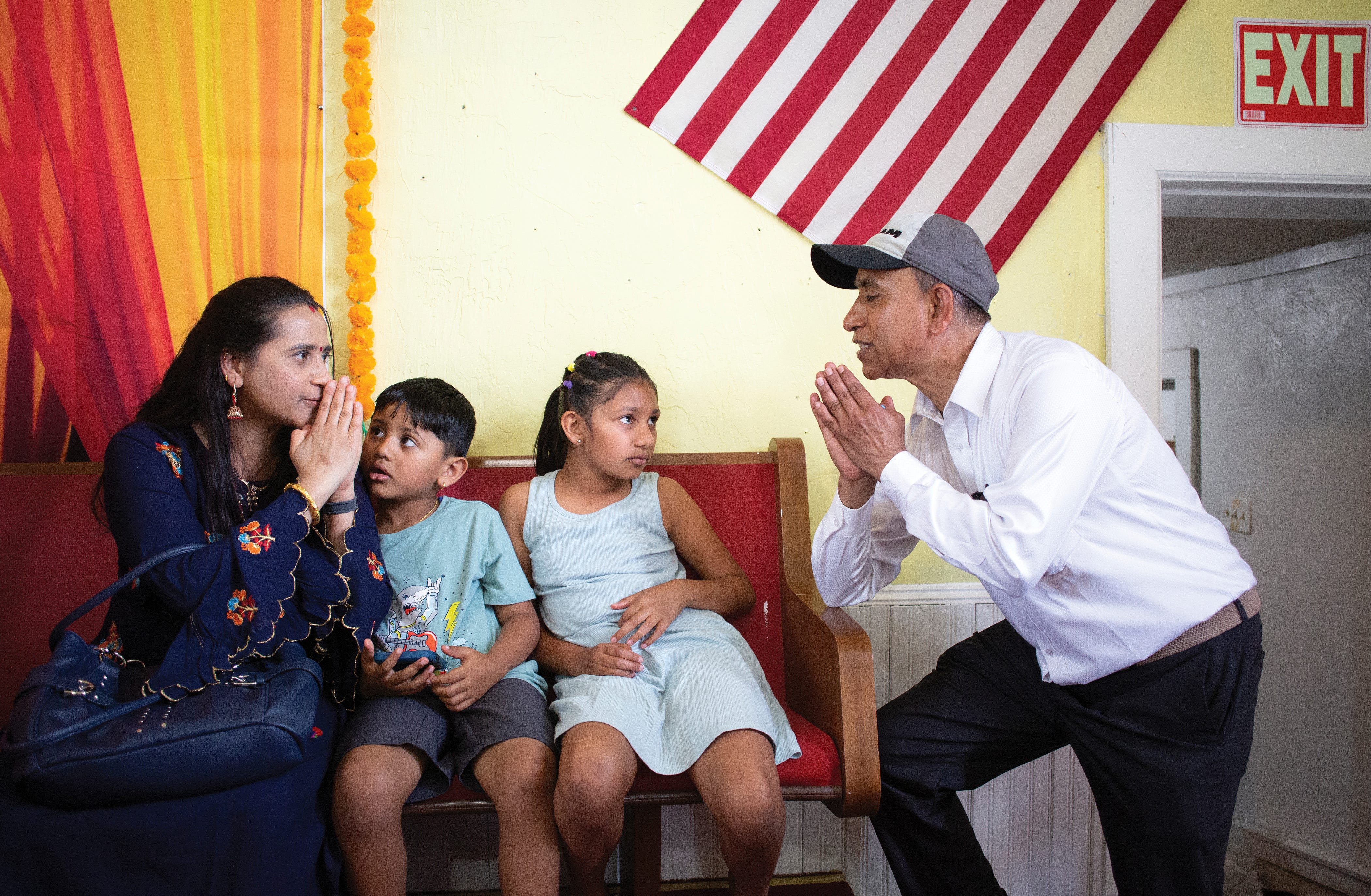 """Ram Upreti greets Hari Gautam and her children Samdeep, 5, and Supriya, 9, with a """"namaste"""" at the non-profit Vedic Welfare Society in Westerville."""