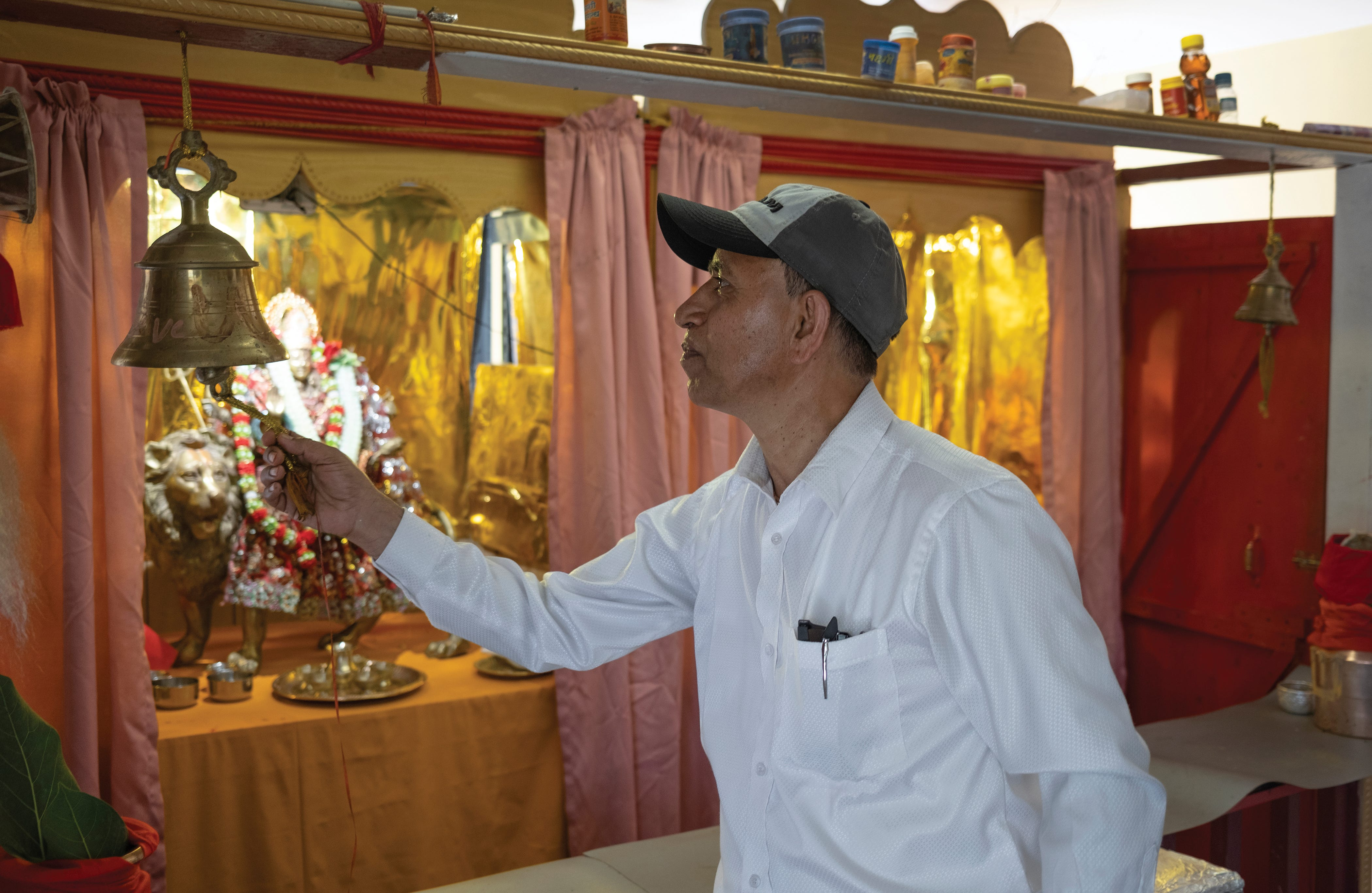 Ram Upreti rings a bell while saying prayers during a Threading Ceremony.