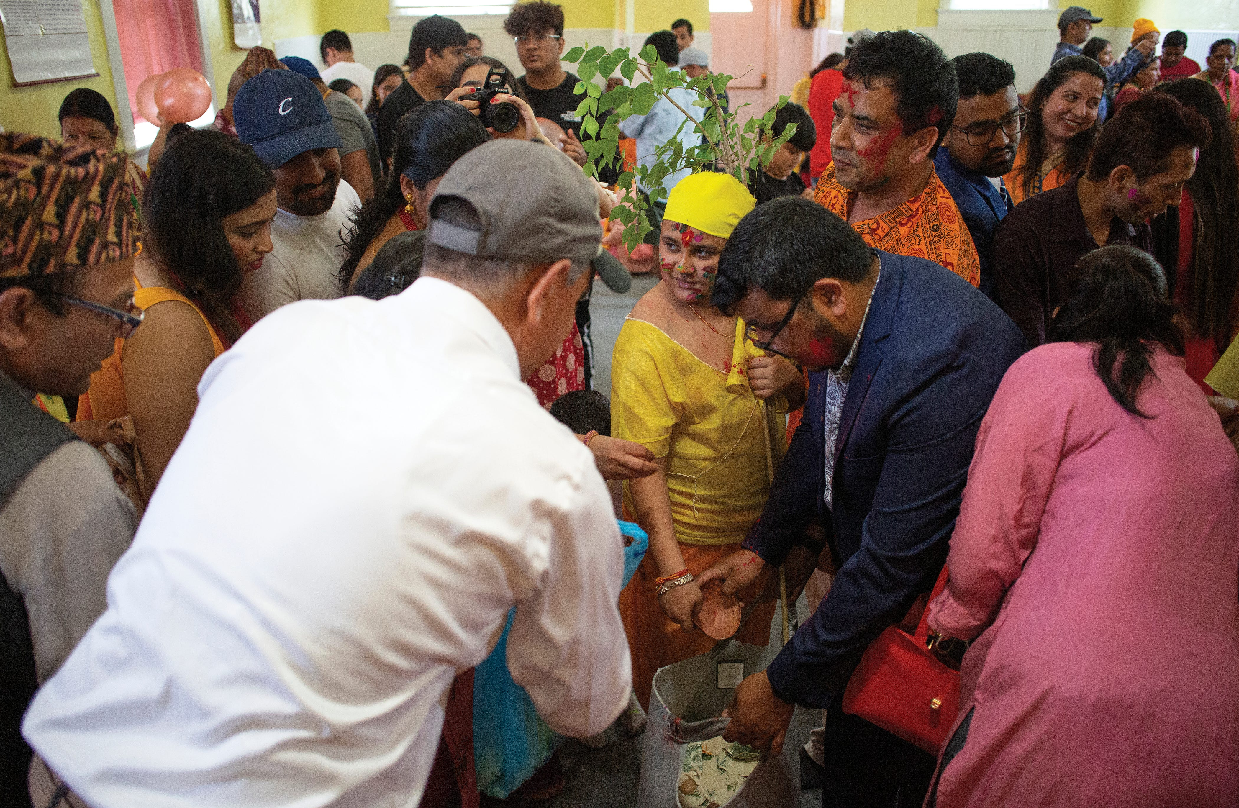 Ram Upreti offers rice and other good for a youngster going through a Threading Ceremony.