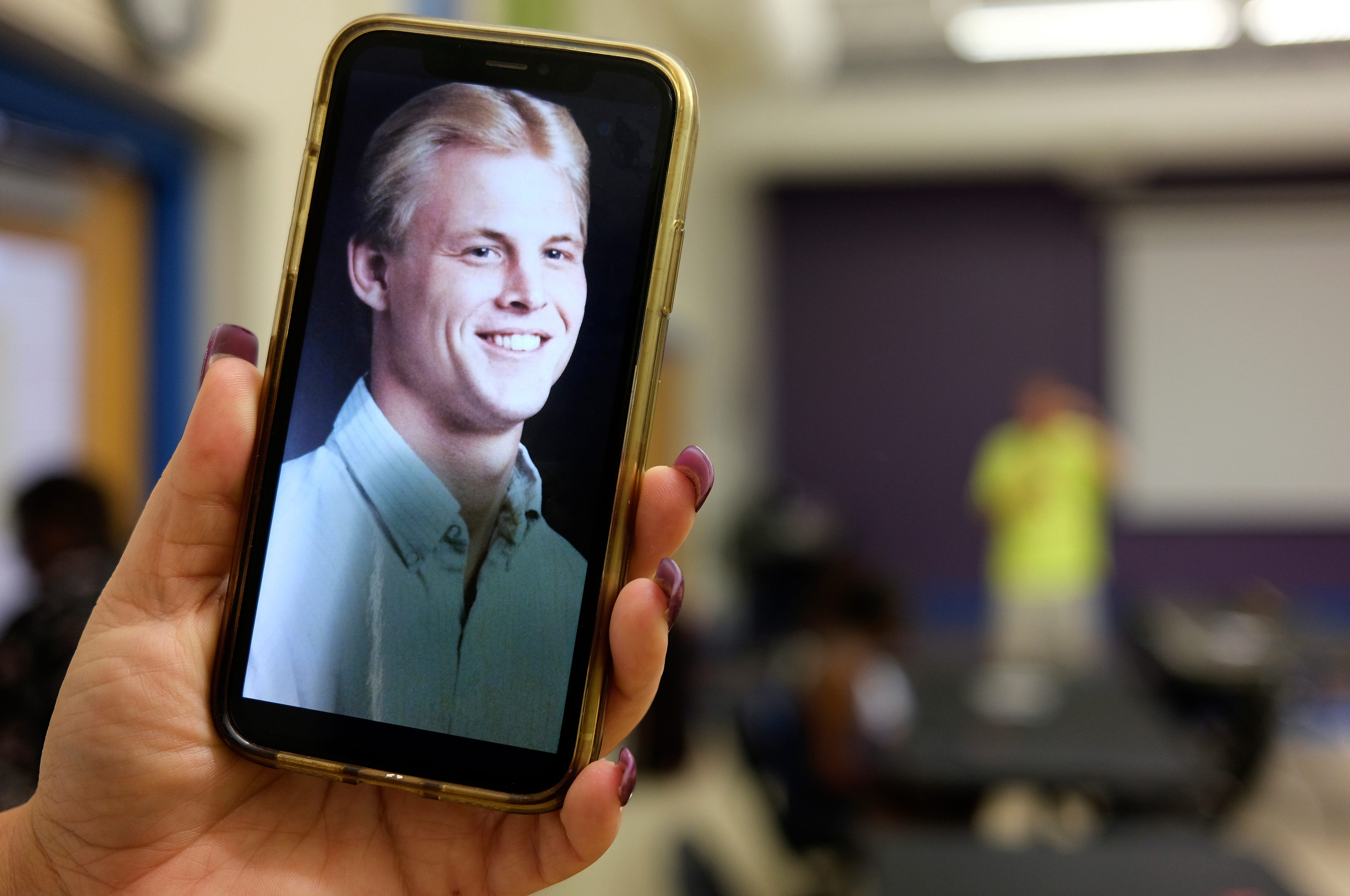 Mindy Baker keeps a photo of Dave Baker as a young man on her cell phone.