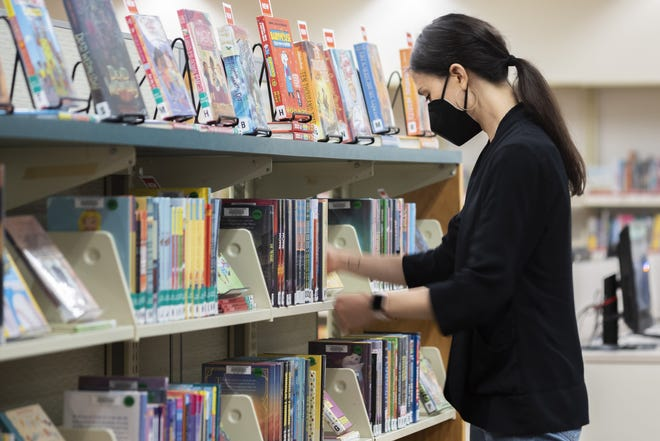Julie Adams, an information services specialist, organizes books in the children's section at the Columbus Metropolitan Library's Whetstone Branch. As cases of the delta variant of the COVID virus begin to rise nationally, the library now requires all staff regardless of vaccination status to wear masks inside buildings and is strongly encouraging patrons to wear a mask inside as well.