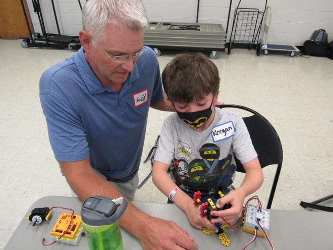 Andy Moore, aroboticsengineering teacher at New Albany intermediate and middle schools, teaches Keegan Guy, 7, how to build a simple robots Aug. 2 in the Thompson Community Center in Columbus. Moore spends his summer teaching children 6 to 14 the basics of coding and building robots through RoboThink, an educational program for which he is the central Ohio franchisee.
