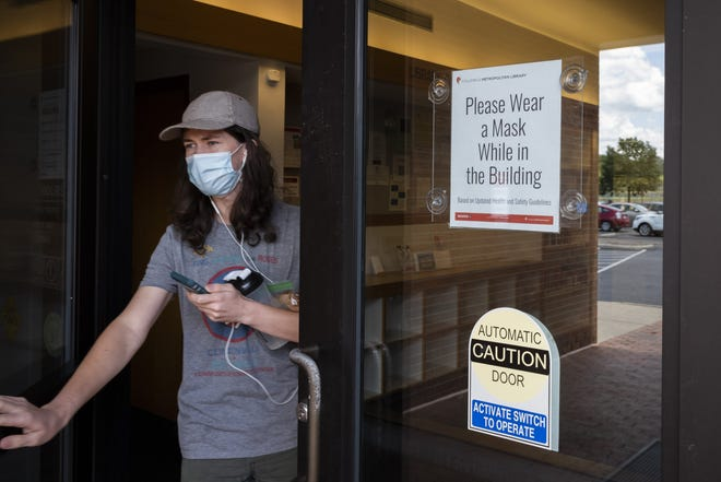 At right, a sign encourages patrons to wear a mask inside as Parker Wilkinson, 16, walks out of the Columbus Metropolitan Library Whetstone Branch on Tuesday, Aug. 3.