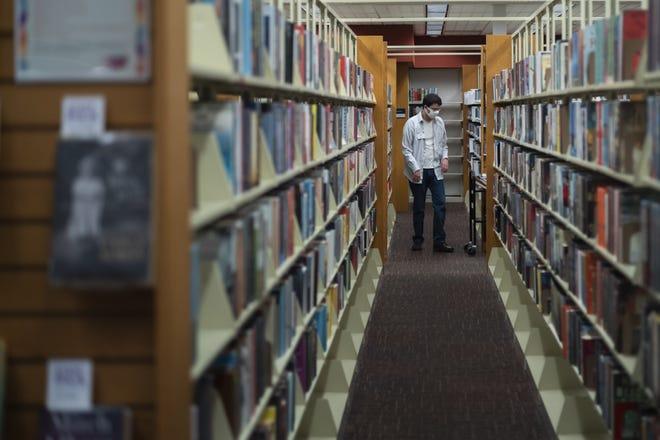 A staff member walks through the shelves at the Columbus Metropolitan Library Whetstone Branch on Aug. 3 in Columbus, Ohio.