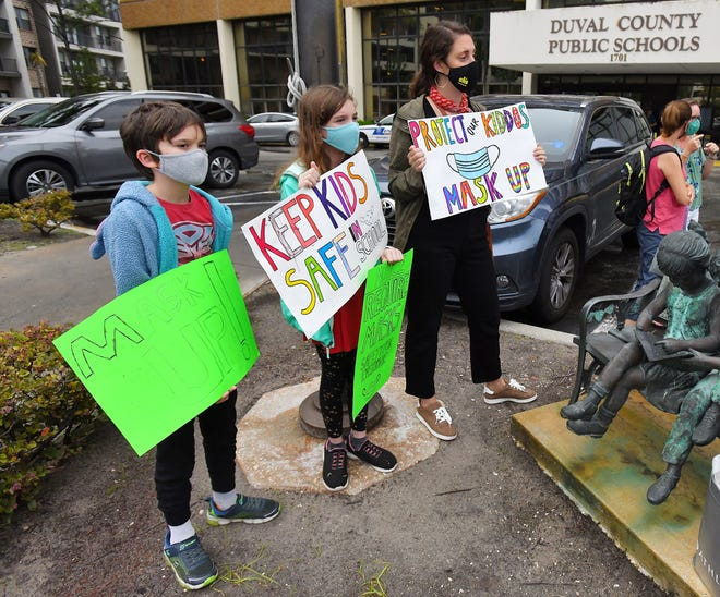 Will Hartley, 10, Lila Hartley, 12 and Gabby Waxman hold their signs in support of masking in schools at a rally before Tuesday evening's school board building.