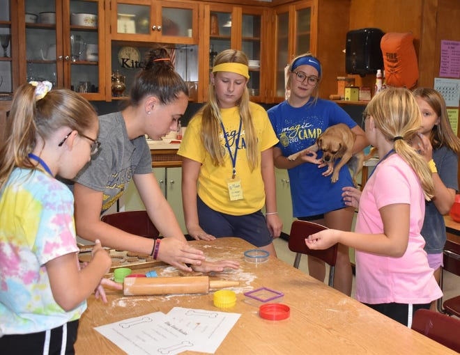 Cambridge FFA hosted mAGic Camp 2021 for fourth and fifth graders at Cambridge Jr./Sr. High School. On Wednesday, July 21, one of the sessions was devoted to making dog treats in the consumer sciences classroom. From left are Leighton Nelson, Kendra Downing, Anna Doubet, Maddie Harrell (holding the official taste tester, a puggle named Zamboni), Adelyn Blade in front and Leah VanDeKamp in back.