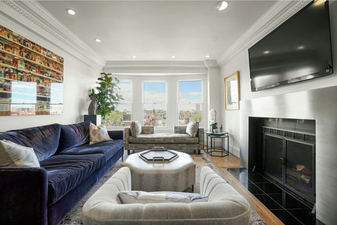 The living room boasts a double crown molding and a woodburning fireplace framed in a modern stainless steel mantel.