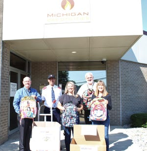 Employees with Michigan Gas Utility display their collection of school supplies. They are (left to right): Mike Baker, Major Wayne Ruston, Shannon Burzychi, Scot Clawson and Renee Burzynski.