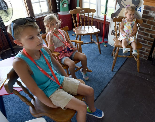 Gabriel Witbeck, 8, and his sisters Elliott, 6, and Charlotte, 3, listen to the story of the Little Brown Bear at The Little Brown Bear House at the Monroe County Fair.
