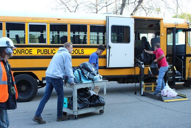 "Branden Martin and Vince Tedrick, DTE volunteers, wheel backpacks onto a Monroe Public Schools bus during the ""Stuff the Bus"" program."
